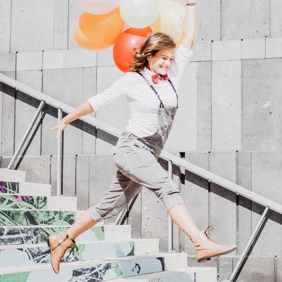 11Nancy springt mit Luftballons in der Hand über Stiegen
